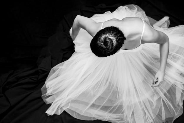 Scala di grigi di seduta della ballerina dell'angolo alto Foto Gratuite