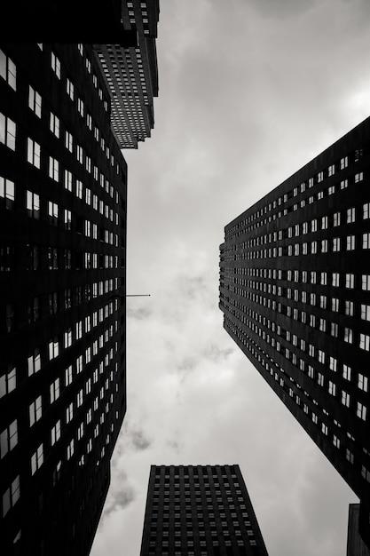 Scala di grigi verticale di angolo basso delle costruzioni della città con un cielo nuvoloso nei precedenti Foto Gratuite
