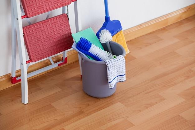 Scala e attrezzature per la pulizia sul pavimento di legno Foto Premium
