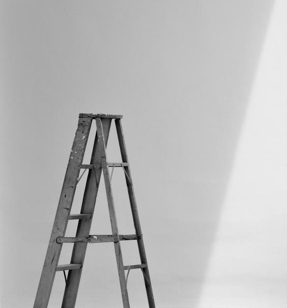 Scala pieghevole in alluminio e l'ombra al muro di cemento bianco Foto Premium
