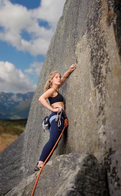 Scalatore femminile che si arrampica con la corda su una parete rocciosa Foto Premium