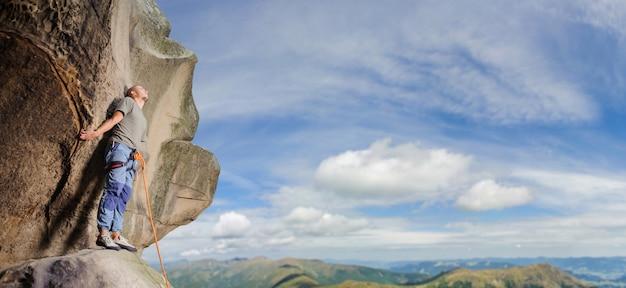Scalatore maschio che scala grande masso in natura con la corda Foto Premium