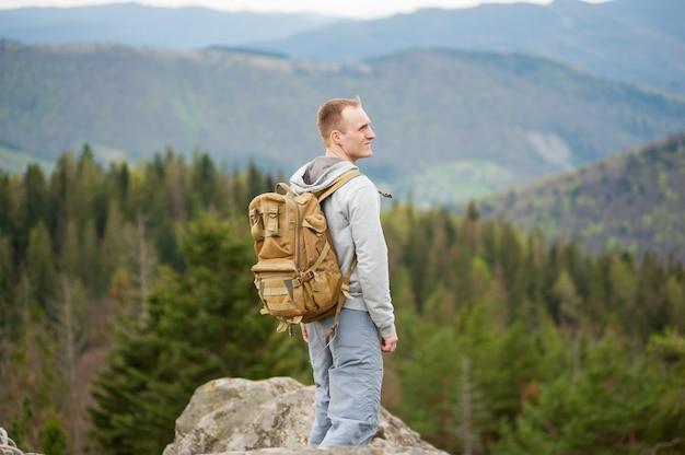 Scalatore maschio con zaino marrone sulla cima della roccia Foto Premium