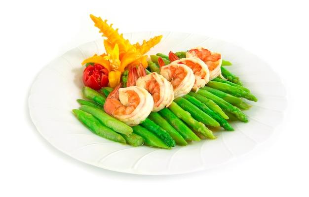 Scalpore di asparagi fritti con gamberetti decorano il peperoncino giallo e il pomodoro intagliato in stile vista laterale Foto Premium