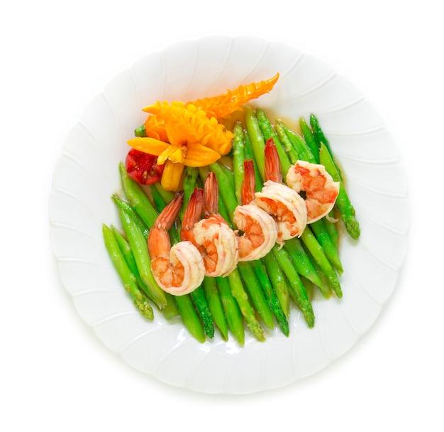 Scalpore di asparagi fritti con gamberi decorano il peperoncino giallo e il pomodoro intagliato stile vista dall'alto Foto Premium