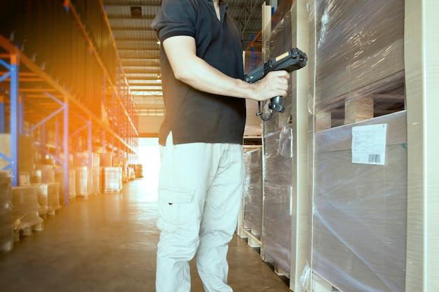 Scanner del codice a barre della tenuta del lavoratore del magazzino con controllo del pallet del prodotto. Foto Premium