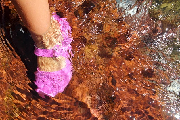 Scarpa rosa piedi d'acqua ragazza in fondo rosso fiume flusso Foto Premium