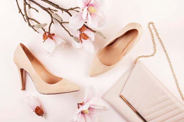 Scarpe con tacchi color nudi e fiori di magnolia Foto Premium