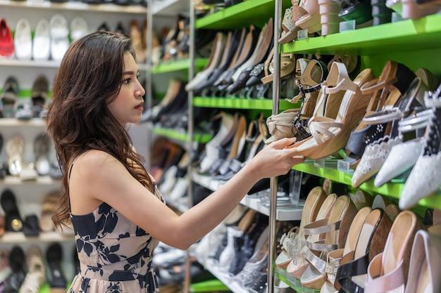 Scarpe d'acquisto del tacco alto della giovane donna in negozio Foto Premium
