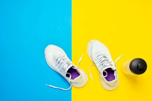 Scarpe da corsa bianche e una bottiglia di acqua su una superficie gialla e blu astratta. concetto di corsa, allenamento, sport. . vista piana, vista dall'alto Foto Premium