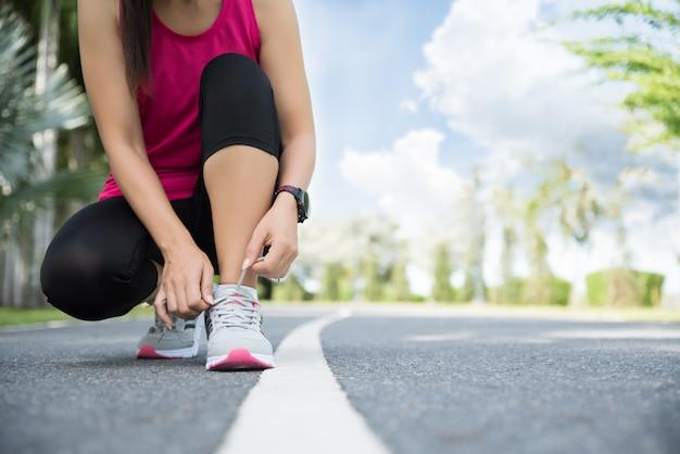Scarpe da corsa - primo piano della donna che lega i laccetti in giardino. Foto Premium