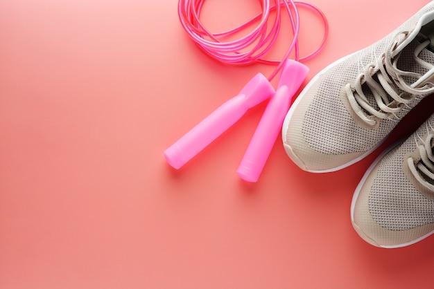 Scarpe da ginnastica e corda per saltare su sfondo rosa Foto Premium