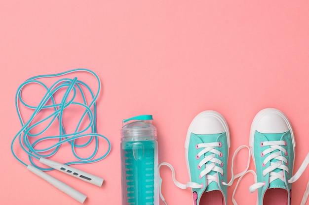 Scarpe da ginnastica turchesi e una corda da salto ad alta velocità sul rosa Foto Premium