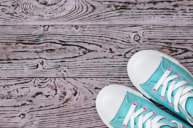 Scarpe da ginnastica turchine e rosa sul pavimento di legno. Foto Premium