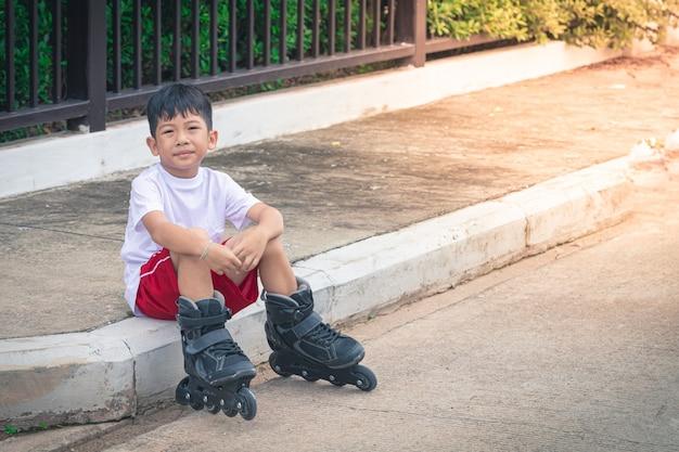 Scarpe da portare del rollerblade di seduta del ragazzo asiatico Foto Premium