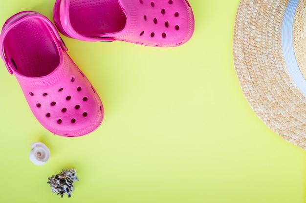 Scarpe da spiaggia, cappello, conchiglie su sfondo giallo. sandali con conchiglie, accessori per le vacanze estive. Foto Premium