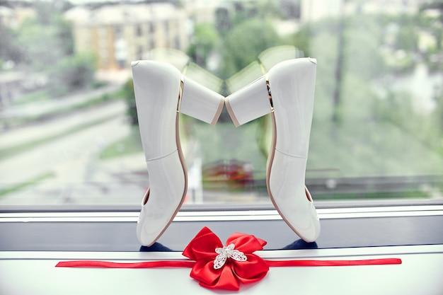Scarpe da sposa e giarrettiera sulla finestra della sposa Foto Premium