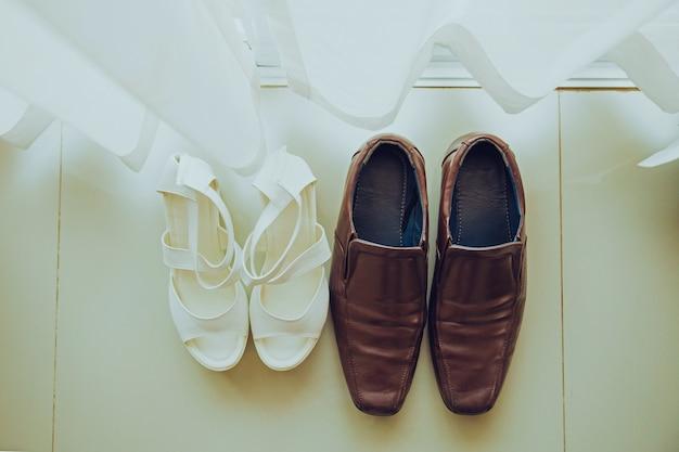 Scarpe da sposo marroni e scarpe da sposa bianche posizionate sul pavimento Foto Premium