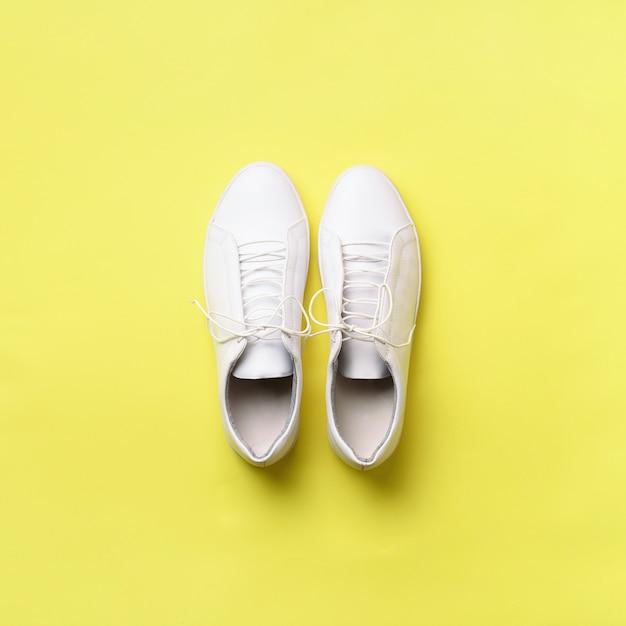 Scarpe da tennis e corda bianche alla moda su fondo giallo con lo spazio della copia. Foto Premium