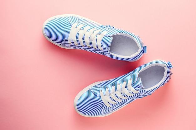 Scarpe da tennis femminili a strisce blu su sfondo rosa pastello. vista piana, vista dall'alto Foto Premium