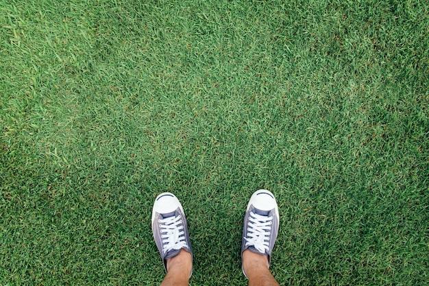 Scarpe da tennis in piedi sull'erba verde, vista dall'alto Foto Premium