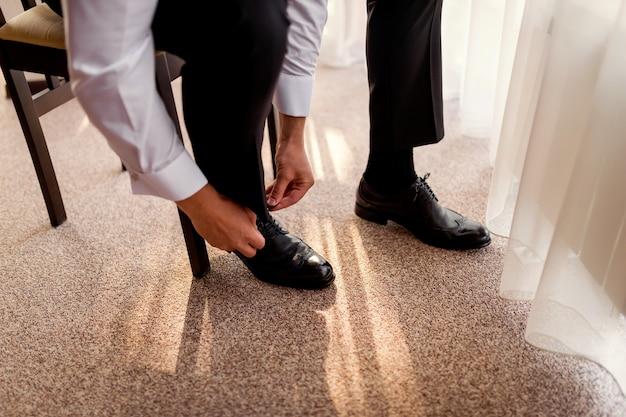 Scarpe da uomo d'affari, uomo che si prepara per il lavoro, sposo mattina prima della cerimonia di nozze Foto Premium