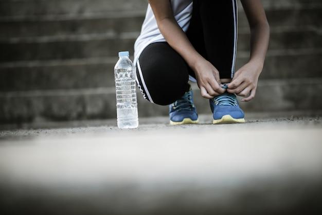 Scarpe da vicino corridore femminile che lega le sue scarpe per un esercizio di jogging Foto Gratuite