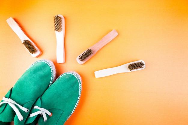 Scarpe espadrillas in pelle scamosciata verde con spazzole su carta gialla. Foto Premium