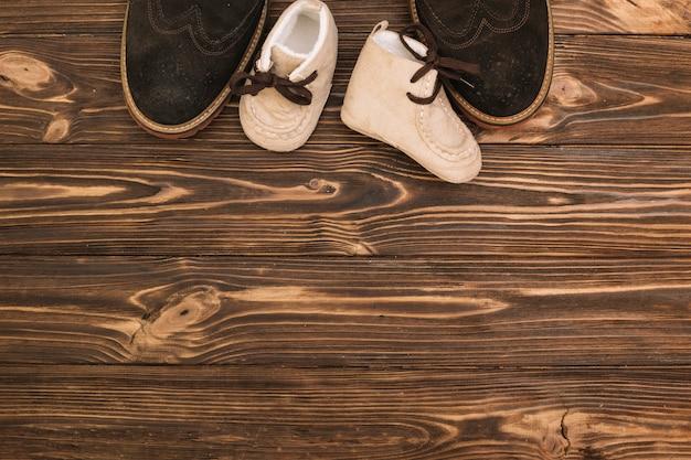 Scarpe maschili vicino a stivali da bambino Foto Gratuite
