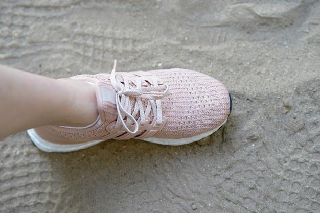 Scarpe runnung rosa su un lato, su sabbia con stampe di scarpe Foto Premium