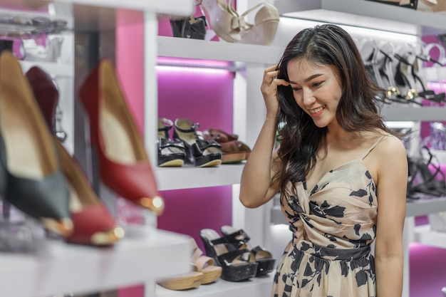 Scarpe shopping donna giovane in negozio Foto Premium