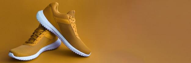 Scarpe sportive su parete color senape Foto Premium