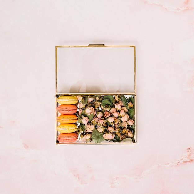 Scatola con boccioli di fiori e biscotti sul tavolo luminoso Foto Gratuite