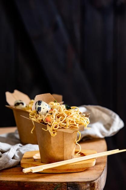 Scatola con noodles e uovo di quaglia su un tavolo Foto Premium