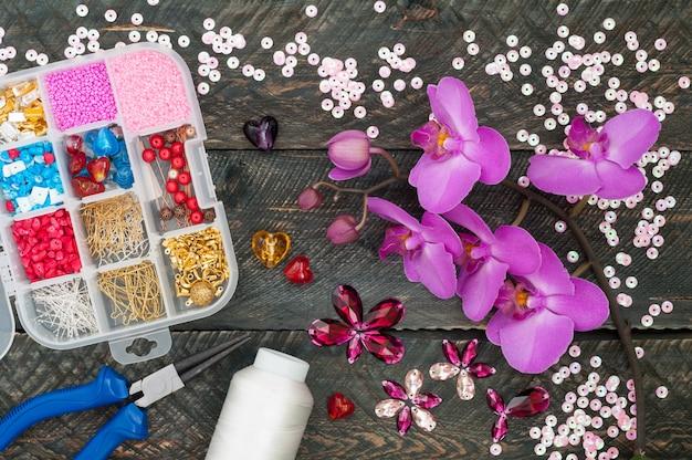 Scatola con perline, rocchetto di filo, pinza e cuori di vetro per creare gioielli fatti a mano su fondo in legno vecchio. accessori fatti a mano. fiori di orchidea Foto Premium
