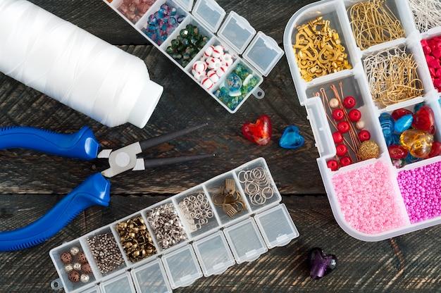 Scatola con perline, rocchetto di filo, pinza e cuori di vetro per creare gioielli fatti a mano su fondo in legno vecchio. accessori fatti a mano Foto Premium
