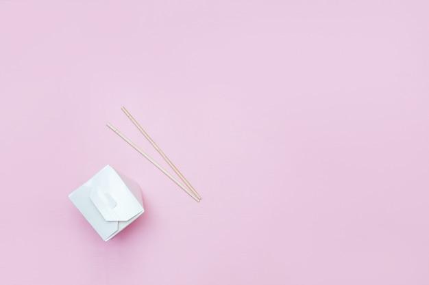 Scatola da asporto aperta per tagliatelle cinesi presentati con le bacchette, su sfondo rosa Foto Premium