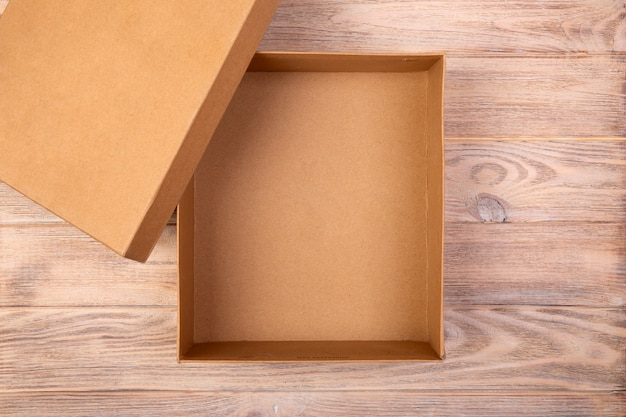 Scatola di cartone aperta su un tavolo di legno. vista dall'alto Foto Premium