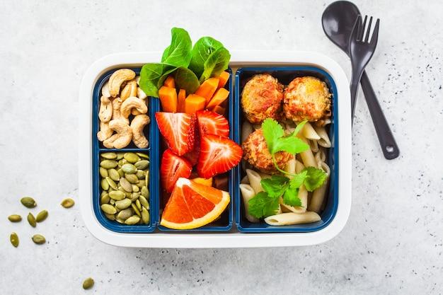 Scatola di cibo sano. cibo vegano: polpette di fagioli, pasta, verdure, bacche, semi e noci in un contenitore Foto Premium