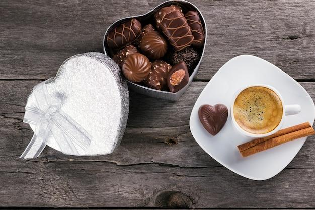 Scatola di cioccolatini, tazza di caffè su un fondo di legno. vista dall'alto Foto Premium