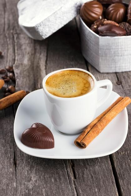 Scatola di cioccolatini, tazza di caffè su un fondo di legno Foto Premium