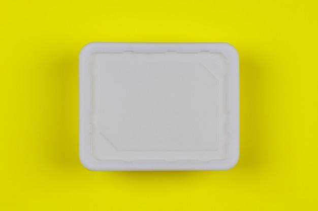 Scatola di plastica bianca del modello sulla vista superiore del fondo giallo Foto Premium