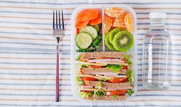 Scatola di pranzo di scuola con sandwich, verdure, acqua e frutta sul tavolo. concetto di abitudini alimentari sane. disteso. vista dall'alto Foto Premium