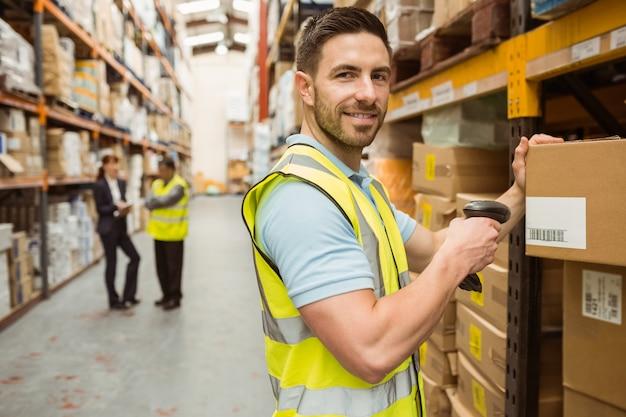 Scatola di scansione del lavoratore del magazzino mentre sorridendo alla macchina fotografica Foto Premium