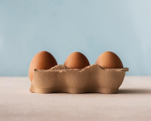 Scatola di vista frontale di uova marroni Foto Gratuite