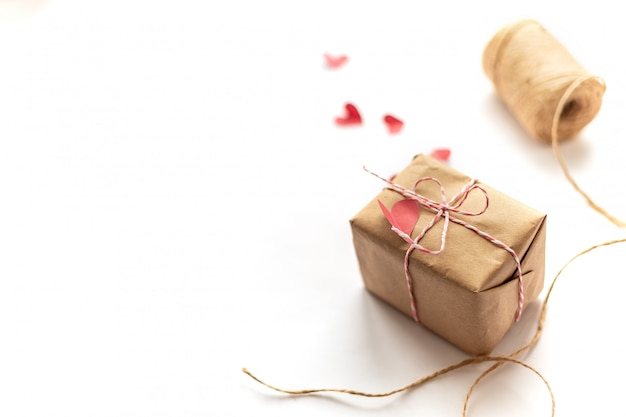 Scatola regalo artigianale che lega l'arco con corda di canapa su cuori bianchi di carta rossa con messa a fuoco selezionata Foto Premium