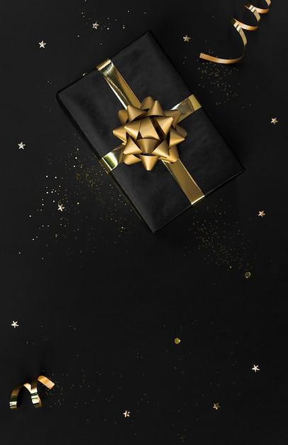 Scatola regalo con decorazioni coriandoli oro su nero per natale e. copyspace Foto Premium