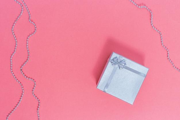 Scatola regalo d'argento. composizione in giorno di s. valentino sul rosa di carta Foto Premium