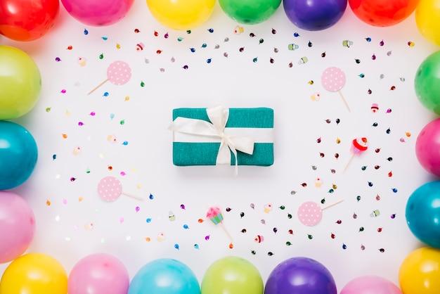 Scatola regalo di compleanno decorata con coriandoli; puntello e palloncini su sfondo bianco Foto Gratuite