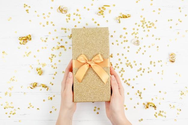 Scatola regalo dorata con coriandoli Foto Premium